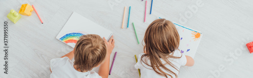 Fototapeta top view of brother and sister in pajamas lying on floor and drawing with felt p