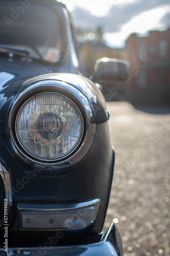 Close-up of a round headlight on an old car. On against the sun © Анатолий Савицкий