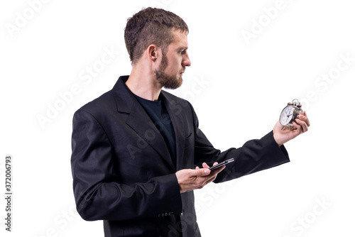 Fototapety, obrazy: A business man in a suit holds a phone and an alarm clock, on a white background.