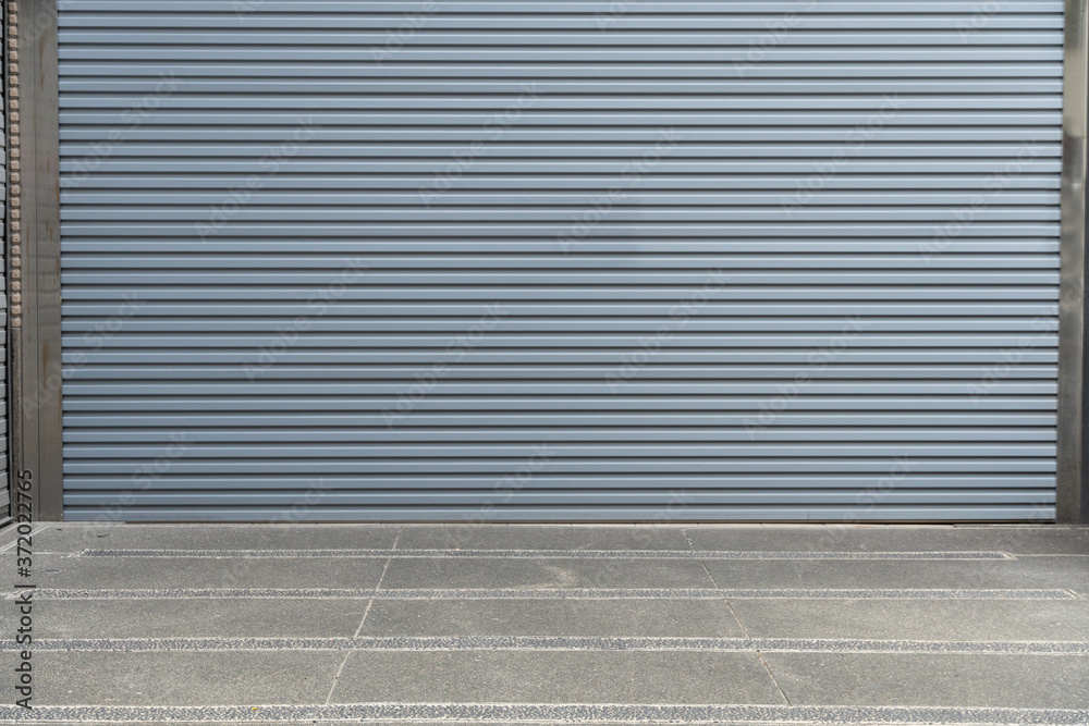 Fototapeta A closeup shot of automatic metal roller door used in factory, storage, garage, and industrial warehouse. The corrugated and foldable metal sheet offer space saving and provide urban and rustic feel
