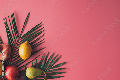 Summer tropical composition made with fresh fruit and green palm leaves on pastel pink background. Flat lay food.