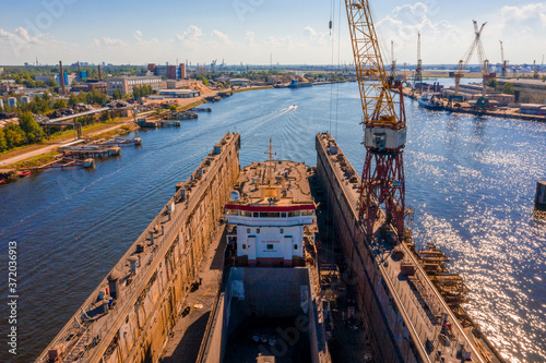 Foto Aerial view of the ship in floating dry dock under repair by sandblasting in Riga, Latvia