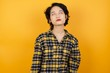 Young asian woman with short hair wearing plaid shirt standing over yellow background looking sleepy and tired, exhausted for fatigue and hangover, lazy eyes in the morning.