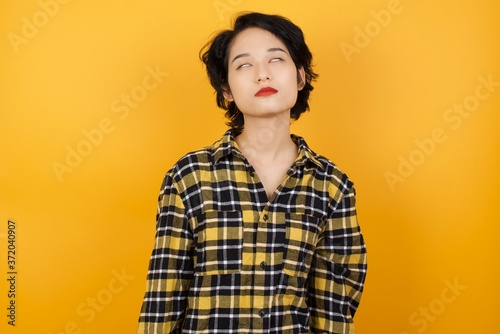 Obraz Young asian woman with short hair wearing plaid shirt standing over yellow background looking sleepy and tired, exhausted for fatigue and hangover, lazy eyes in the morning. - fototapety do salonu