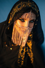 Portrait Of Young Beautiful Oriental Mysterious Girl. The Woman Looks Into The Camera. The Face Is Hidden By A Golden Veil. Luxurious Evening Make-up, Smoky Eyes. The Head Is Covered With Black Scarf