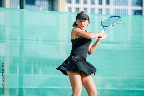 Fotografia, Obraz Active teenage girl playing tennis on a new court, returning ball