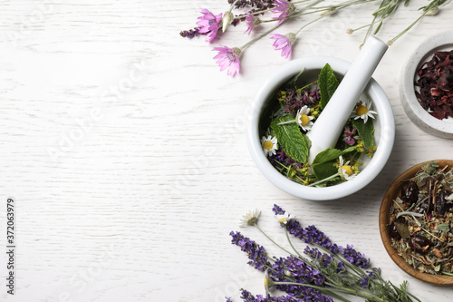 Foto Mortar with healing herbs and pestle on white wooden table, flat lay