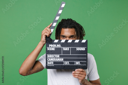 Fotografie, Obraz Funny young african american man guy with dreadlocks 20s in white t-shirt posing covering face with classic black film making clapperboard hiding isolated on green color background studio portrait