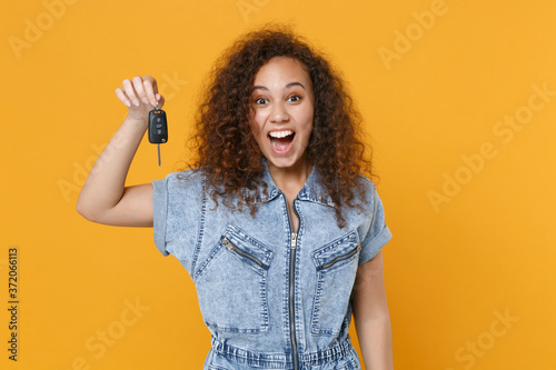 Cuadros en Lienzo Surprised young african american girl in casual denim clothes posing isolated on yellow wall background studio portrait