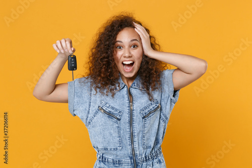 Surprised young african american girl in casual denim clothes isolated on yellow wall background studio portrait Billede på lærred