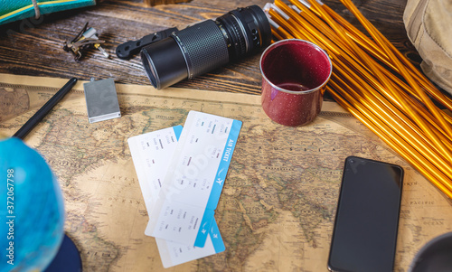 Photo Hiking equipment for tourism and a map of the world with a globe on wooden table
