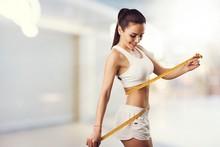 Beautiful Fitness Girl Measuring Her Waistline With Measure Tape