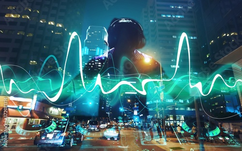 Young dj with headphones with dj equipment on night city background Fototapet