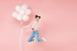 Leinwandbild Motiv Full length portrait happy young woman in casual sweater isolated on pastel pink background. Birthday holiday party people emotions concept. Celebrating hold air balloons jumping doing winner gesture.