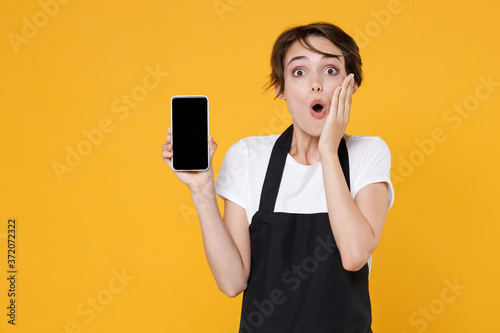 Shocked young female woman 20s barista bartender barman employee in apron hold mobile phone with blank empty screen mock up copy space put hand on cheek isolated on yellow background studio portrait Wallpaper Mural