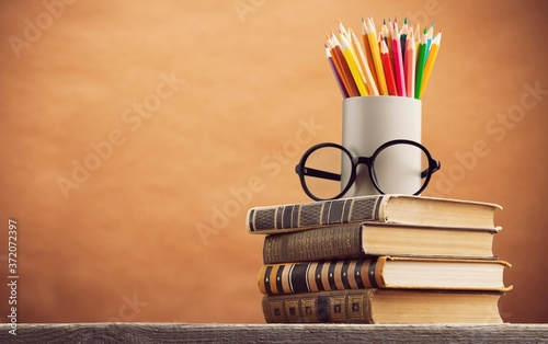Fotografering Stack of vintage books and colorful pencils on the desk