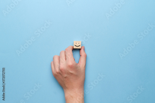 Fotografie, Obraz Good mood smiley concept on a wooden cube with a hand.