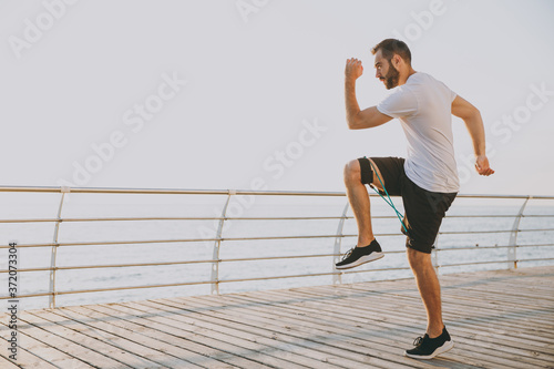 Obraz na plátne Full length portrait handsome attractive young bearded athletic man guy 20s in white t-shirt posing training doing exercises for legs with fitness gums looking aside at sunrise over the sea outdoors
