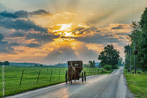 Photo Amish Buggy on Rural Road Early Morning with Sunbeams