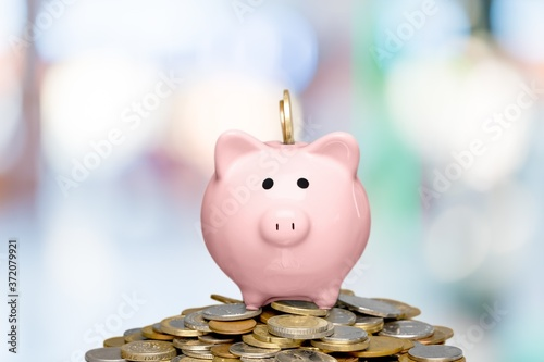Piggy bank and golden coins on blur background Tableau sur Toile