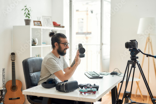 Fotografia, Obraz Male technology blogger holding headphones, showing thumbs up while recording vi