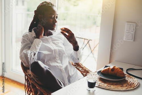 Fototapeta A sexy young black girl with braided hair is sitting on a wicker chair at a kitchen table and having breakfast, eating a delicious bakery; a croissant and a cup of coffee espresso in front of her obraz