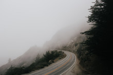 Curved Road By The Ocean Covered In Fog