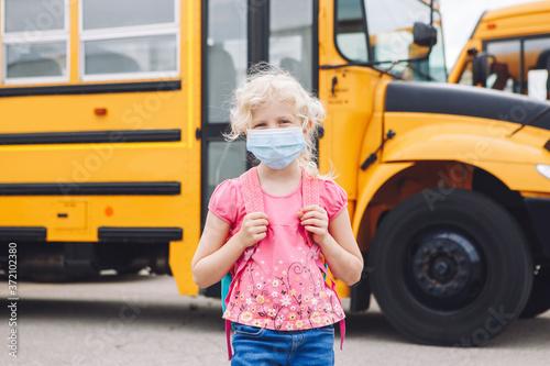 Happy Caucasian girl student wearing face mask near yellow bus Fototapeta