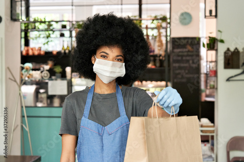 Fototapeta African American hipster waitress wearing face mask and gloves holding takeaway food order in hands giving bag standing in cafe