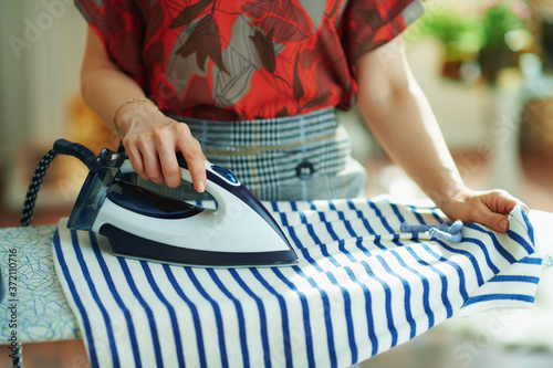 Fotografia trendy woman ironing in house in sunny day