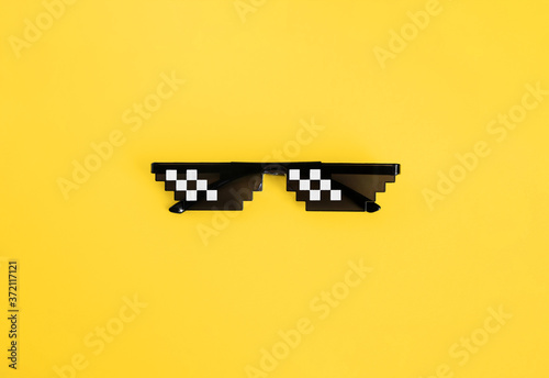 Fotografie, Obraz Funny pixelated boss sunglasses on yellow background