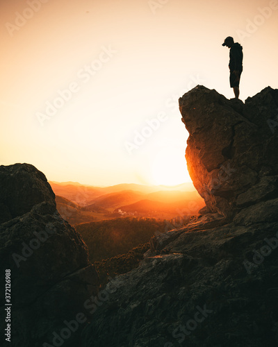 man standing on top of mountain during sunset in summer Fototapet