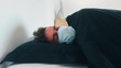 Young caucasian man sleeping with face mask on, COVID-19 coronavirus
