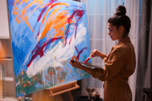 Foto Young artist mixing paint on wooden palette in art studio