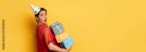 Fototapeta horizontal image of surprised pregnant woman in party car holding stack of prese