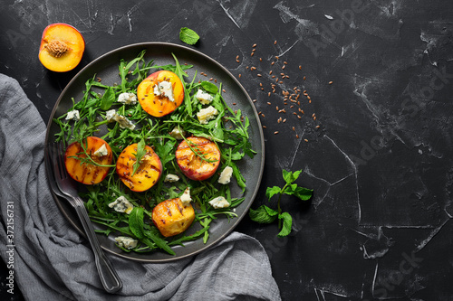 Fresh diet salad grilled peach, arugula and blue cheese in a plate on a black stone background Canvas
