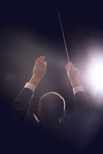 Male Conductor On Dark Background, Back View