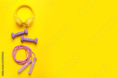 Jumping rope with dumbbells and headphones on color background Fototapet