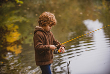 Little Fisherman. Child Boy Fishing In Overalls From A Dock On Lake Or Pond.