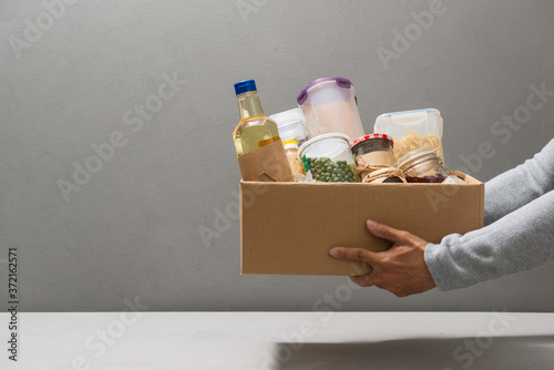 Volunteer in gloves holding food in a donation cardboard box with various food Canvas Print