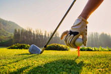 Close Up Hand Asian Woman Putting Golf Ball On Tee With Club In Golf Course On Sunny Day For Healthy Sport. Lifestyle Concept.