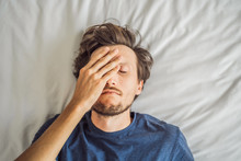 Extremly Tired Young Man Lying On The Bed, Home Alone. Self-isolation At Home, Quarantine Due To Pandemic COVID 19. Mental Health Problems In Self-isolation At Home