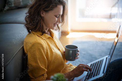 Foto Beautiful young girl woman in a yellow shirt works on a laptop at home in the li