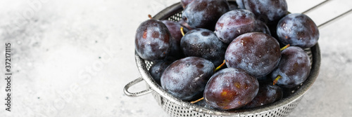 Ripe plum. Lots of plums in a metal bowl on a light background. Blue plums close-up. Healthy fruits. Banner
