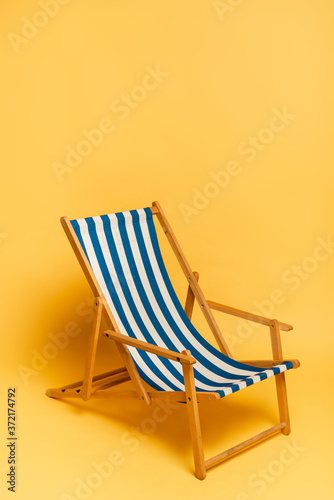 Photo blue and white deckchair on yellow with copy space