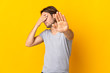 Young handsome man isolated on yellow background making stop gesture and covering face
