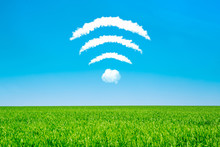 Clouds In The Shape Of A WiFi Symbol On A Blue Sky And Green Meadow Background. Public Free Wi-Fi Concept. Modern Technology