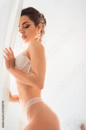 Fototapeta seductive bride in lace underwear and earring touching white curtain obraz na płótnie