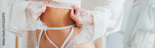 Panoramic shot of bride in silk robe and garter belt touching bra at home Fototapeta