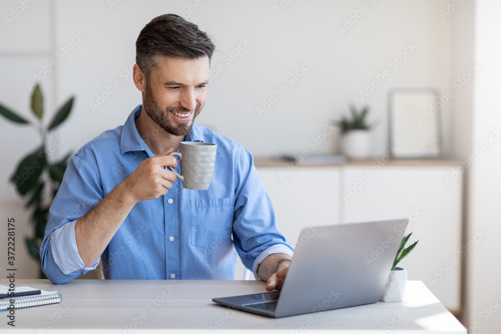 Fototapeta Handsome smiling businessman drinking coffee and using laptop in office, checking emails